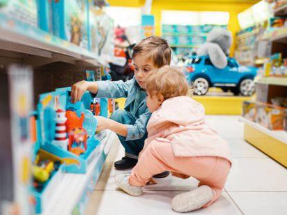 Dos niños eligen varios juguetes en una tienda de juguetes.