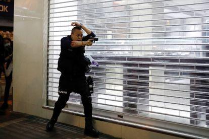 Un policía apunta con su arma a manifestantes en Hong Kong, el pasado 29 de febrero.