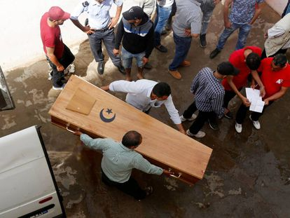 Familiares de un migrante tunecino muerto cargan con su ataúd en la morgue del hospital de Sfax.