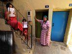 Dos niñas muestran las solicitudes de inscripción escolar en su casa del barrio melillense de La Cañada, junto a su abuela.