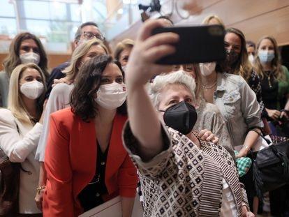 Una mujer se hace un autorretrato con la presidenta de la Comunidad de Madrid, Isabel Díaz Ayuso, en la Asamblea de Madrid el pasado 8 de junio.