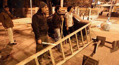 Jóvenes egipcios con palos y bastones bloquean una calle de El Cairo para proteger su propiedad ante los saqueadores
