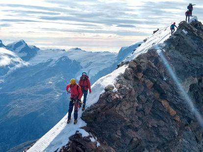 El guía argentino Tomi Aguiló y su clienta Elisa recorren el camino entre la cima suiza y la italiana.