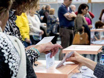 Una mujer deposita su voto en una urna.
