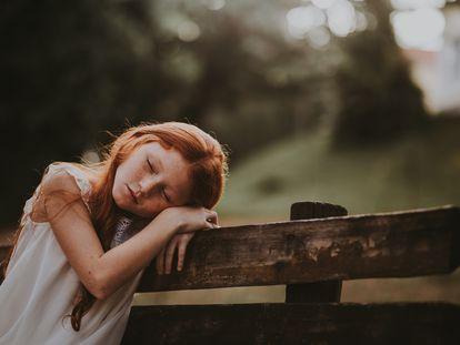 Una niña se duerme en un banco.