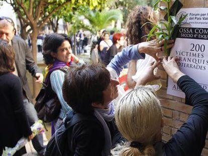 Miembros del Fòrum de la Memòria colocan carteles en el Cementerio General de Valencia.