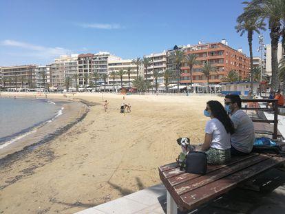 Una pareja, en la playa de Torrevieja, municipio alicantino donde priman las segundas residencias.
