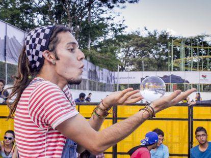 Un joven hace malabares con una esfera de cristal en el Festival Altavoz de Medellín.