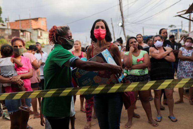 Una mujer recoge comida donada por una ONG este viernes en Brasilandia, una de las mayores favelas de São Paulo.