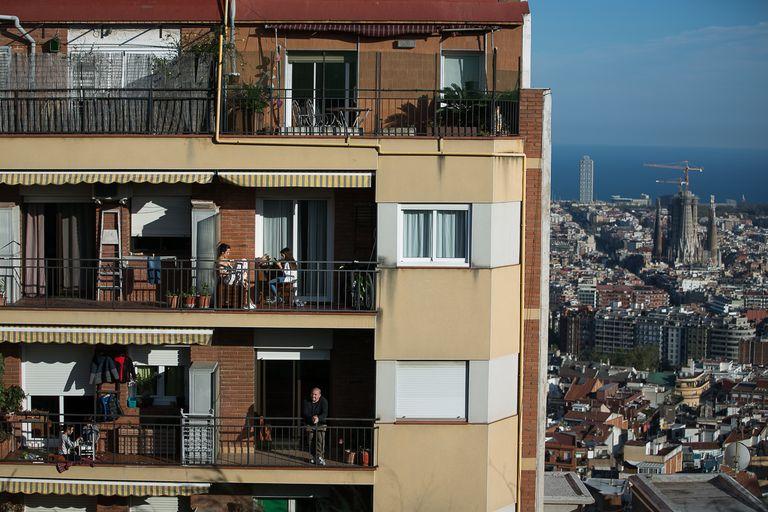 Los vecinos de este edificio de Barcelona se asoman a sus terrazas durante el confinamiento.