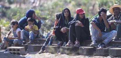 Un grupo de extranjeros esperan este lunes en la frontera griega para cruzar a Macedonia.