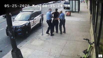 Dos policías llevan a George Floyd al coche patrulla junto al que murió más tarde el 25 de mayo de 2020. El vídeo del que se sacó esta imagen se mostró durante el juicio del agente Derek Chauvin por la muerte de Floyd.