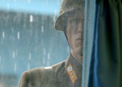 Un soldado norcoreano mira a través de una ventana al interior del edificio de la ONU que separa las dos Coreas durante la visita de la secretaria de Estado, Hillary Cliton, y el secretario de Defensa, Robert Gates, en julio de 2010.