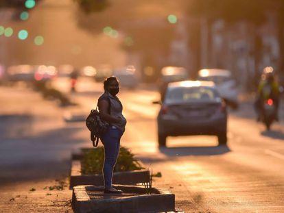 Una mujer con una mascarilla espera sobre una avenida de Ciudad de México.