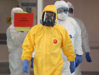 Vladímir Putin (con traje protector amarillo) visita un hospital de Moscú que trata a pacientes afectados por la Covid-19, este martes.