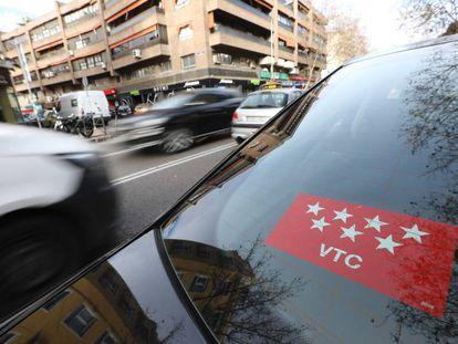 Un vehículo de transporte con conductor circula por las calles de Madrid.