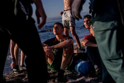 Un grupo de menores migrantes, sentados en la playa tras llegar a nado a Ceuta, espera en la arena rodeados de dos agentes de la Guardia Civil, el 19 de mayo.