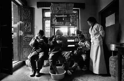 La enfermera tibetana Tenzin Yankyi en el Viejo Centro de Acogida en Katmandú (Nepal) atiende a tres niños recién llegados que sufren congelación después de cruzar el paso de Nangpa La, escapando de Tíbet.