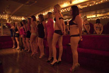 Prostitutas exhibiéndose para los clientes en un club.