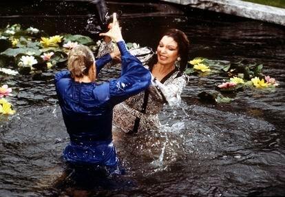 Krystle (Linda Evans) y Alexis (Joan Collins), en una de las esperadas peleas de gatas de la serie, esta vez en el estanque de nenúfares de la mansión Carrington lily pond. |