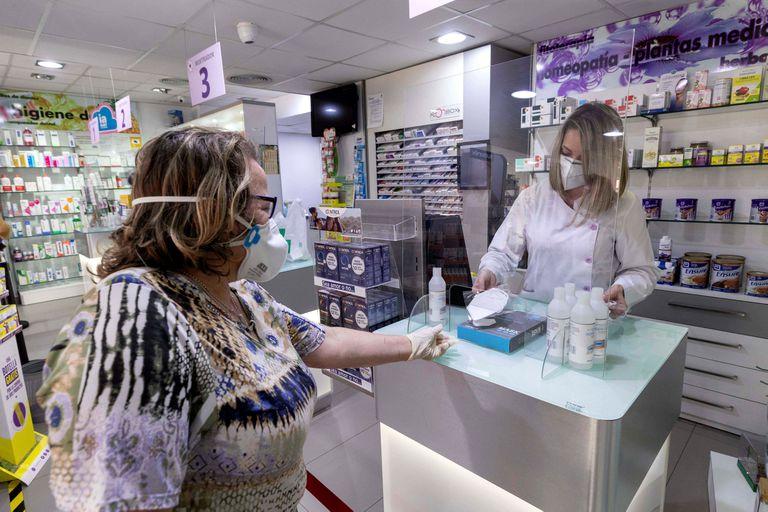 Una mujer compra una mascarilla en una farmacia de Archena (Murcia).