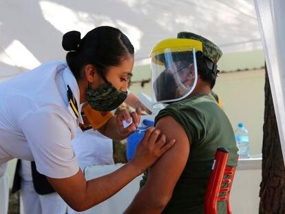 La enfermera Mercedes José aplica una inyección a un militar este domingo 27 de diciembre.