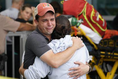 Una pareja se abraza tras el colapso del edificio en Surfside.
