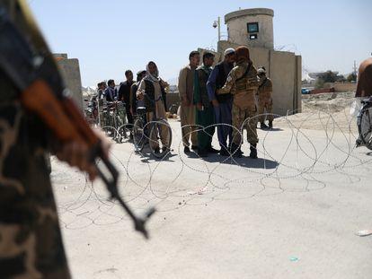 Guerrilleros talibanes cachean a los trabajadores que abandonan el aeropuerto de Kabul, este domingo.