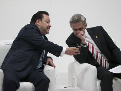 Héctor Serrano, secretario de Gobierno, muestra su teléfono al jefe de Gobierno Miguel Ángel Mancera, en enero de 2014.