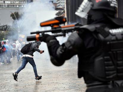 Un agente de la policía antidisturbios dispara hacia los manifestantes en la plaza Bolívar de Bogotá en las protestas de la huelga nacional, este miércoles.