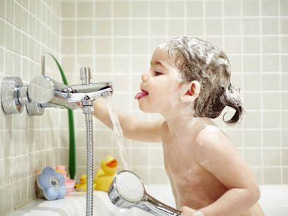 Bebé en la bañera intentando beber agua del grifo.
