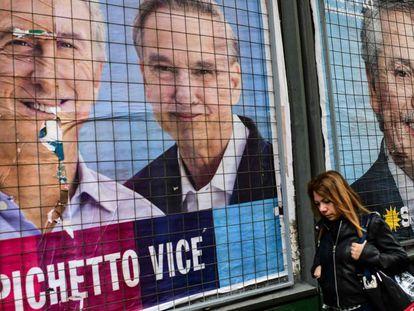 Una mujer pasa por delante de carteles de propaganda de Mauricio Macri y Alberto Fernández en una calle de Buenos Aires.