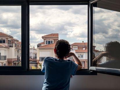 Un niño mira por la ventana, en una imagen de archivo.