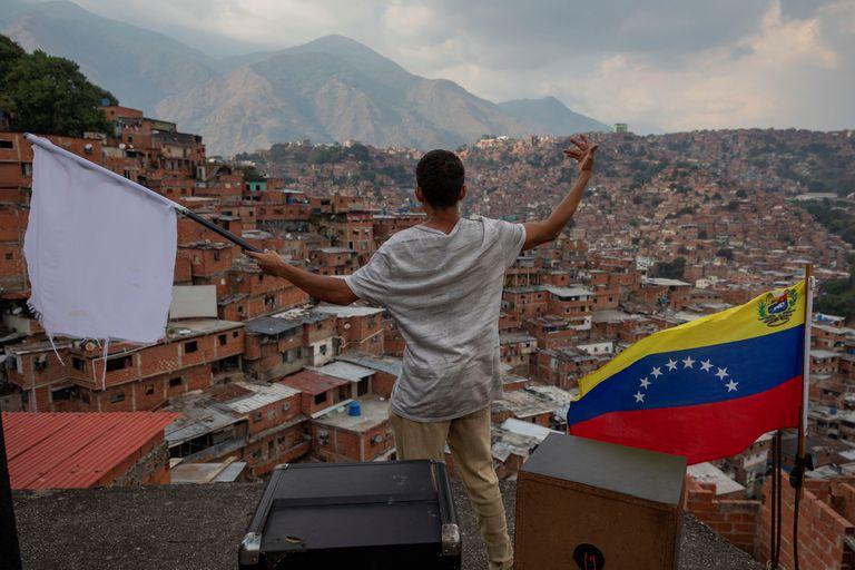 Un hombre ondea una bandera blanca desde el techo de una casa en el barrio José Félix Ribas de Petare, Caracas.