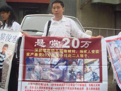 Un ciudadano chino sostiene un cartel con fotos de niños desaparecidos