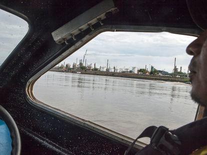 Una embarcación de transporte navega por el Río Magdalena con la refinería de Barrancabermeja de fondo.