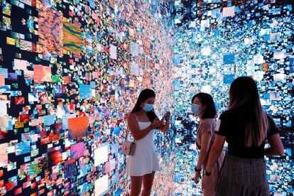 Tres visitantes a la Feria de Arte Digital de Hong Kong junto a una obra inmersiva de Refik Anadol que se convertirá en un certificado digital único (NFT) y se subastará en Sotheby's.