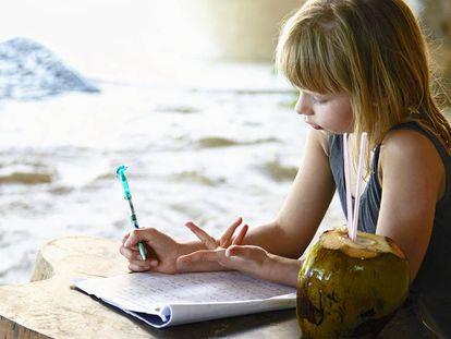 Niña hace deberes en verano.