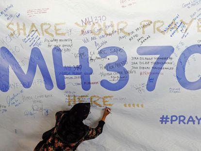 Una mujer escribe un mensaje para los pasajeros del avión desaparecido en 2014.