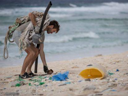 Un hombre, miembro de un grupo de voluntarios medioambientalistas, recoge residuos en una playa de la isla deshabitada de Henderson, en el sur del Océano Pacífico.