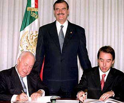 Jesús de Polanco, a la izquierda, y Emilio Azcárraga Jean firman la alianza en presencia de Vicente Fox.
