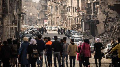 Un grupo de personas camina por una calle de Alepo./ En vídeo, un analista advierte del riesgo de una rápida retirada de las tropas estadounidenses en Siria.