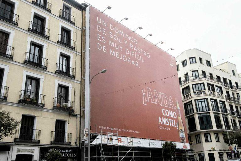Una lona publicitaria tapa la fachada de un edificio en la Plaza del Cascorro, en La Latina