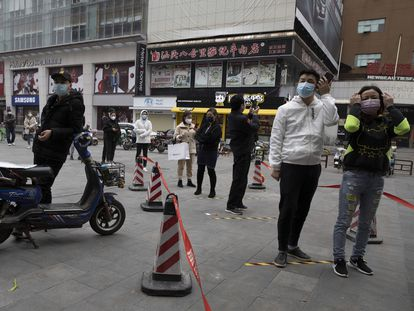 Residentes de Wuhan guardan cola para entrar en un supermercado.