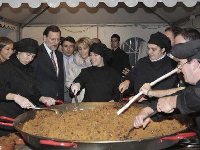 Rajoy observa cómo se preparan las migas del pastor que se sirvieron en la cena del PP de Madrid.