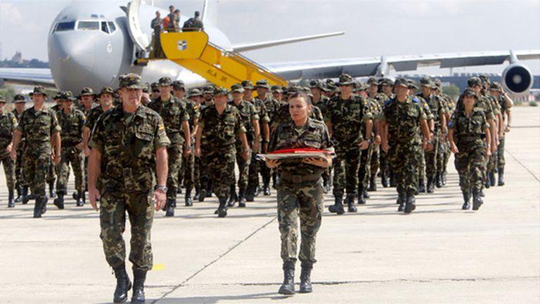 El coronel Blázquez y una soldado portan la última bandera española que ondeó en Istok de la misión, a su regreso en la base aérea de Getafe.
