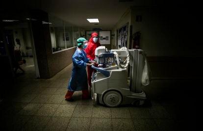 Dos trabajadores del hospital trasladan una unidad móvil de radiodiagnóstico por un pasillo del hospital.
