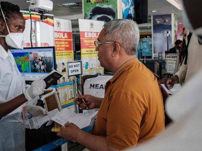 Una trabajadora sanitaria del aeropuerto de Entebbe, en Uganda, comprueba los documentos de un viajero que acaba de llegar al país. En vídeo, declaraciones del presidente de Sudáfrica, Cyril Ramaphosa.