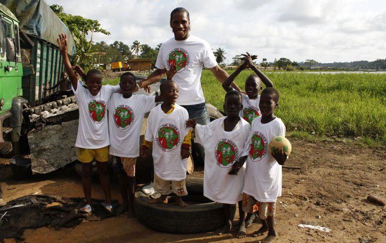 Didier Drogba posa con unos niños de su fundación, en Costa de Marfil.