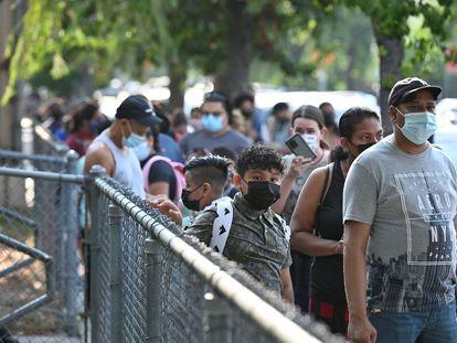 Padres y alumnos esperan para entrar a una escuela el 16 de agosto, el día de vuelta a clases en California.